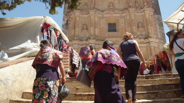 two women walking to the clothing and craft stalls by the town church in san cristobal de las casas, chiapas, mexico - bright stock videos & royalty-free footage