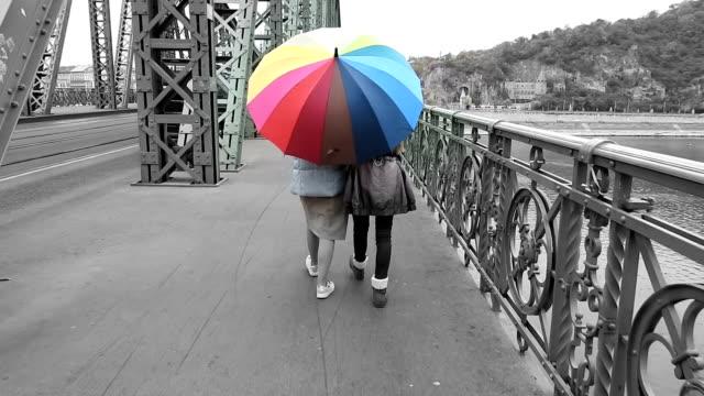 due donne che camminano sotto l'ombrello arcobaleno - ombrello video stock e b–roll
