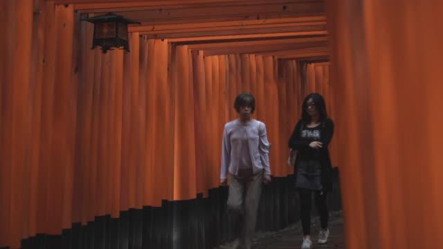 MS Two women walking under Torii gates leading to inner Fushimi Inari Taisha shrine, Kyoto, Japan