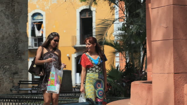 vidéos et rushes de ms two women walking with shopping bags, merida, yucatan, mexico - cadrage aux genoux