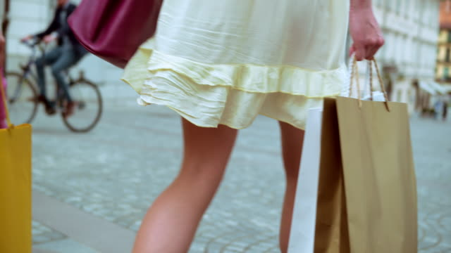 slo mo two women walking with shopping bags - shopping bag stock videos & royalty-free footage