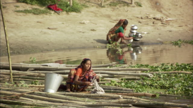 MS, Two women washing clothes and pots in river, Bangladesh