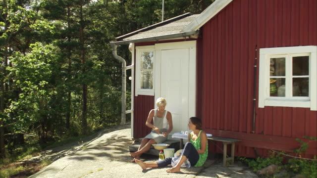 stockvideo's en b-roll-footage met two women washing up the dishes outdoors blido stokholm arhchipelago sweden. - huisje