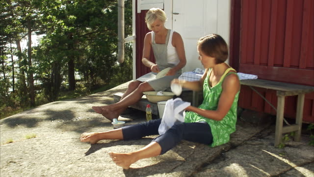 two women washing up the dishes outdoors blido stokholm arhchipelago sweden. - washing up stock videos & royalty-free footage