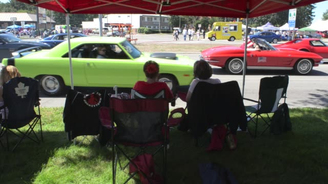 / two women watch a parade of classic cars during under a canopy at the 17th annual woodward dream cruise / detail of cars / woodward dream cruise is... - frisiertes auto stock-videos und b-roll-filmmaterial