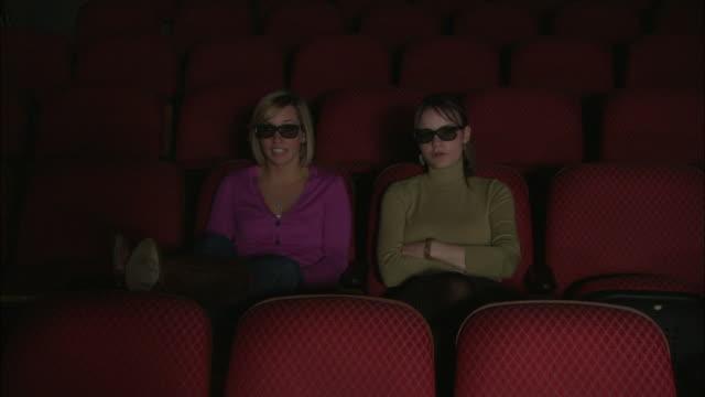 ms two women watching 3d movie, brooklyn, new york city, usa - 膝から上の構図点の映像素材/bロール