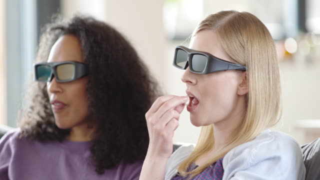 two women watching a 3d movie and eating popcorn - 3d glasses stock videos & royalty-free footage