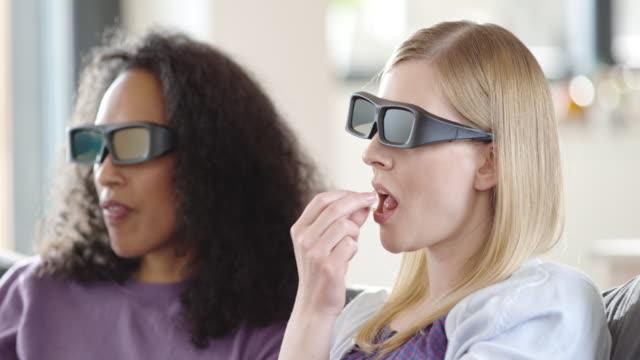 vídeos de stock, filmes e b-roll de duas mulheres assistindo a um filme 3d e comendo pipoca - óculos de terceira dimensão