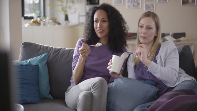 two women watching a movie and eating ice cream - spoon stock videos & royalty-free footage