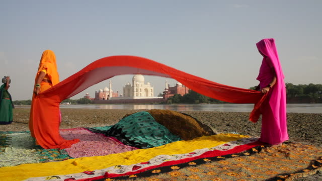 Two women wave a colorful sari between them within sight of the Jumna Yamuna River.