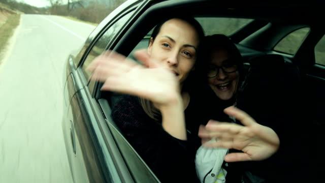 Two women waving in car