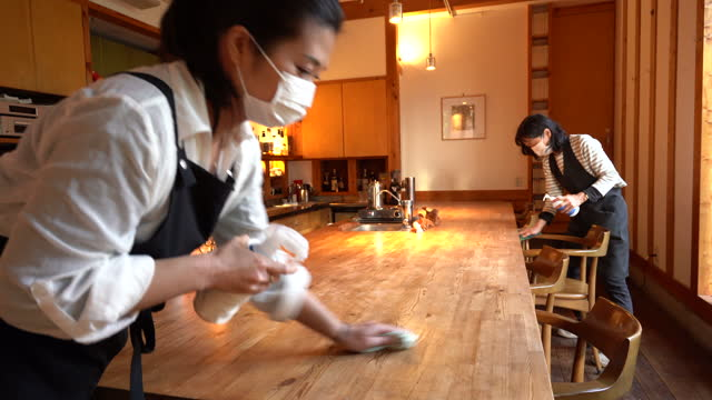 two women wearing a mask, carefully wipe a counter  and enthusiastically disinfect in preparation for opening - ponytail stock videos & royalty-free footage