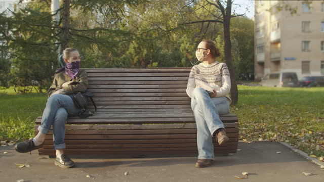 two women wearing disposable protective mask or bandana face covering and sitting on a bench with social distancing - park bench stock videos & royalty-free footage