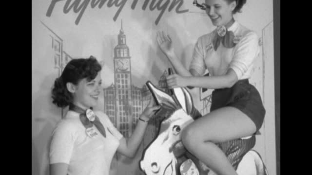 Two women wearing identical outfits of shorts one riding standing donkey model holding onto ears and laughing drawing of city scene backdrop with...