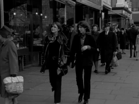stockvideo's en b-roll-footage met two women wearing jackets and trousers walk along a street and into a clothes shop 1967 - kleding