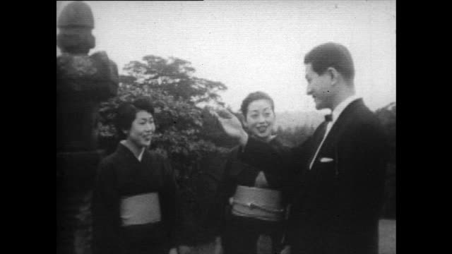 two women wearing kimonos politely greet a man in suit; 1958 - obedience stock videos & royalty-free footage