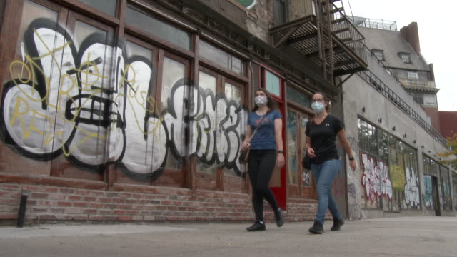 two women wearing protective masks over their faces walk past several shuttered businesses covered in graffiti on 7th avenue south on september 26... - scott mcpartland stock videos & royalty-free footage