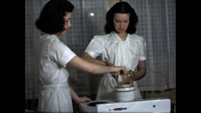 stockvideo's en b-roll-footage met two women wearing white dresses stir and pour food over stove - home economics