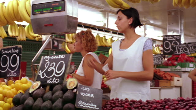 two women weighing + bagging fruit behind fruit stand / barcelona, spain - greengrocer stock videos & royalty-free footage