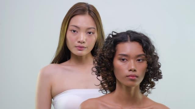 vídeos de stock, filmes e b-roll de duas mulheres com pele brilhante fazendo expressões faciais - cor de cabelo
