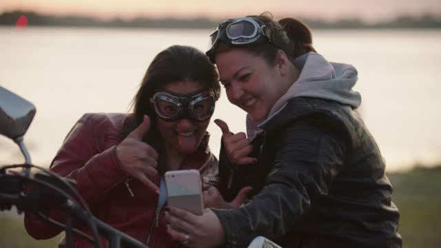 vídeos y material grabado en eventos de stock de two women with motorcycle take funny smartphone selfies by riverside. - motociclista