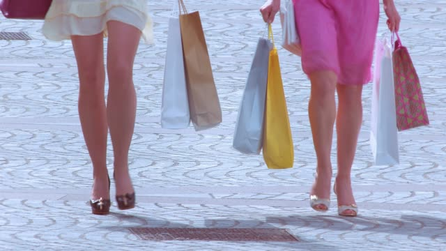 Two women with shopping bags walking down the street