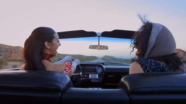ms. two women with vintage style look at each other and laugh in classic convertible on vegas road trip. - formal glove stock videos & royalty-free footage