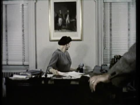 vídeos de stock e filmes b-roll de 1955 ms b/w two women working in office, answers the phone / usa - 1955