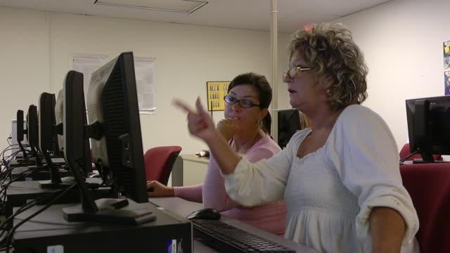 MS Two women working on computer class lab at state run job retraining center / Jackson, Michigan, United States
