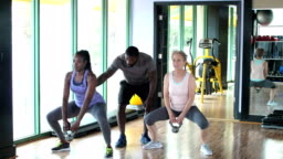 Two women working out together with fitness instructor