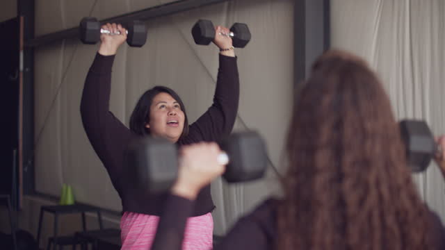 cu two women working out with dumbbells together - dedication stock videos & royalty-free footage