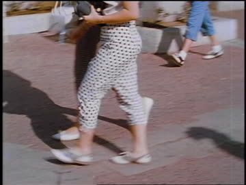 1957 pan two women's legs in clamdiggers walking outdoors / feature - 1957 stock videos & royalty-free footage