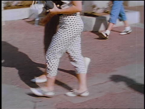 1957 pan two women's legs in clamdiggers walking outdoors / feature - pants stock videos and b-roll footage