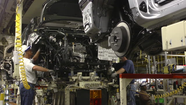 ms two workers align and installing  engine in minivan chassis at an auto assembly plant / princeton, indiana, united states - motore video stock e b–roll