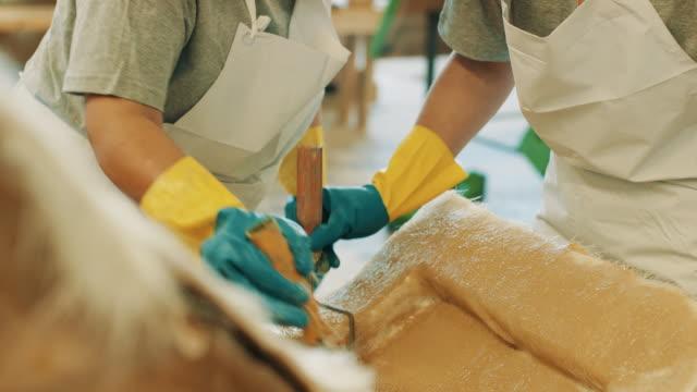stockvideo's en b-roll-footage met twee werknemers epoxy toe te passen op plexiglas mal met rollen - foam hand