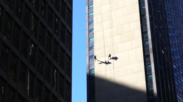 two workers are hanging on the high-rise building wall by rope for facade inspection among the midtown manhattan skyscrapers at new york ny usa on nov. 14 2018. - hanging stock videos & royalty-free footage