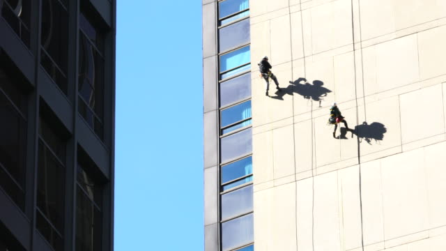 two workers are hanging on the high-rise building wall by rope for facade inspection among the midtown manhattan skyscrapers at new york ny usa on nov. 14 2018. - gebäudefront stock-videos und b-roll-filmmaterial