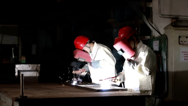 two workers are working on electric welding - shield stock videos and b-roll footage