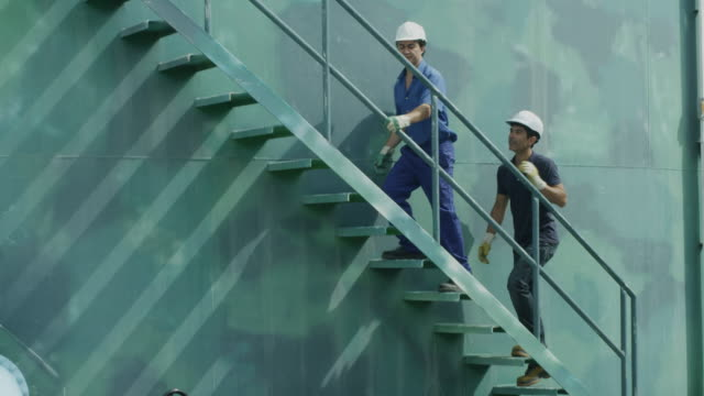 ls two workers ascending stairs on storage tank; camera follows them up, red r3d 4k - staircase stock-videos und b-roll-filmmaterial