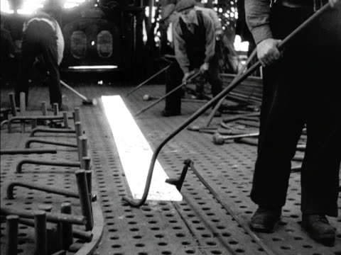two workers beat a white hot strip of metal at the port glasgow shipyards - serving utensil stock videos and b-roll footage