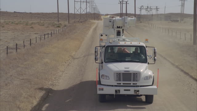 ws ts aerial two workers driving through dirt road / hooker, ok, usa - schotterstrecke stock-videos und b-roll-filmmaterial