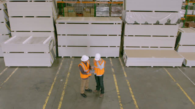 HA two workers facing camera, standing in warehouse in front of stacked goods, talking, looking at tablet computer