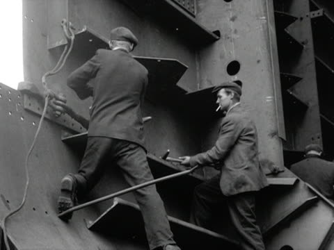 Two workers hammer large rivets into part of a ship at the Port Glasgow shipyards