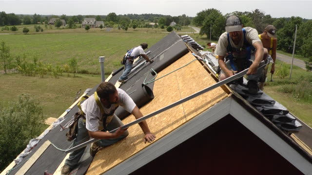 ms two workers hammering edgework on roof of red building / chelsea, michigan, united states - provincial reconstruction team stock videos & royalty-free footage