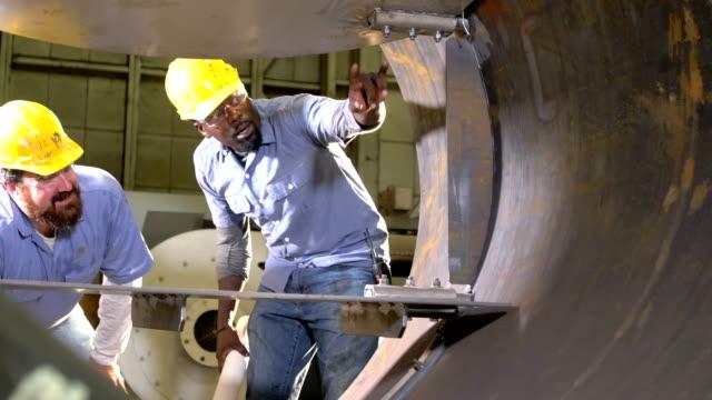 stockvideo's en b-roll-footage met twee werknemers in de fabriek inspectie van grote metalen object - manufacturing occupation