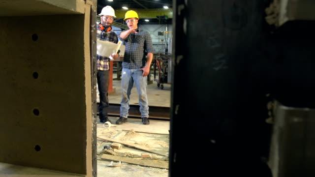 zwei arbeiter in lagerhalle prüfen pläne - zeichnen stock-videos und b-roll-filmmaterial