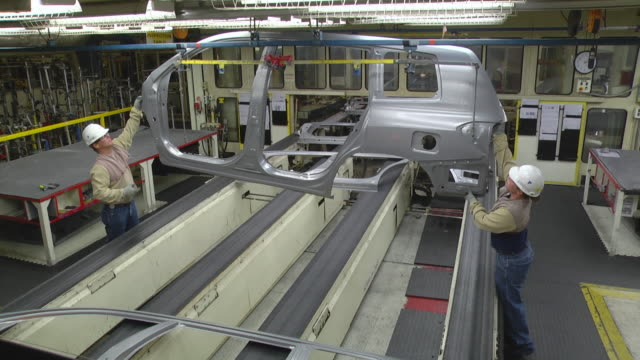 MS PAN Two Workers inspect sheet metal stampings before they are welded together to form mini van / Princeton, Indiana, United States