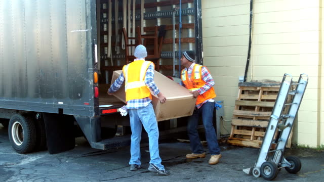 two workers loading big box onto delivery truck - sollevare video stock e b–roll