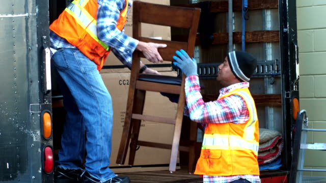 Two workers loading furniture onto delivery truck
