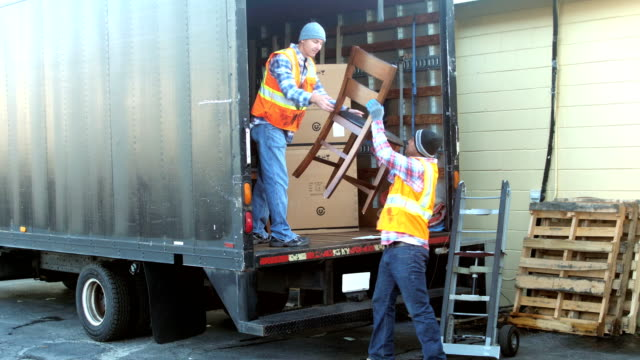 two workers loading furniture onto delivery truck - removal man stock videos & royalty-free footage
